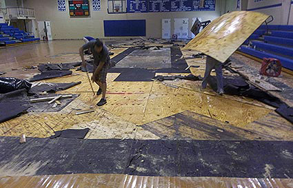 Technicians removing gym flooring