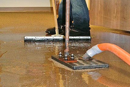 Perfection Property Restoration Commercial Services technician using a water claw to extract water from flooring
